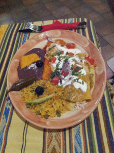 Enchiladas served with rice and refried black beans.