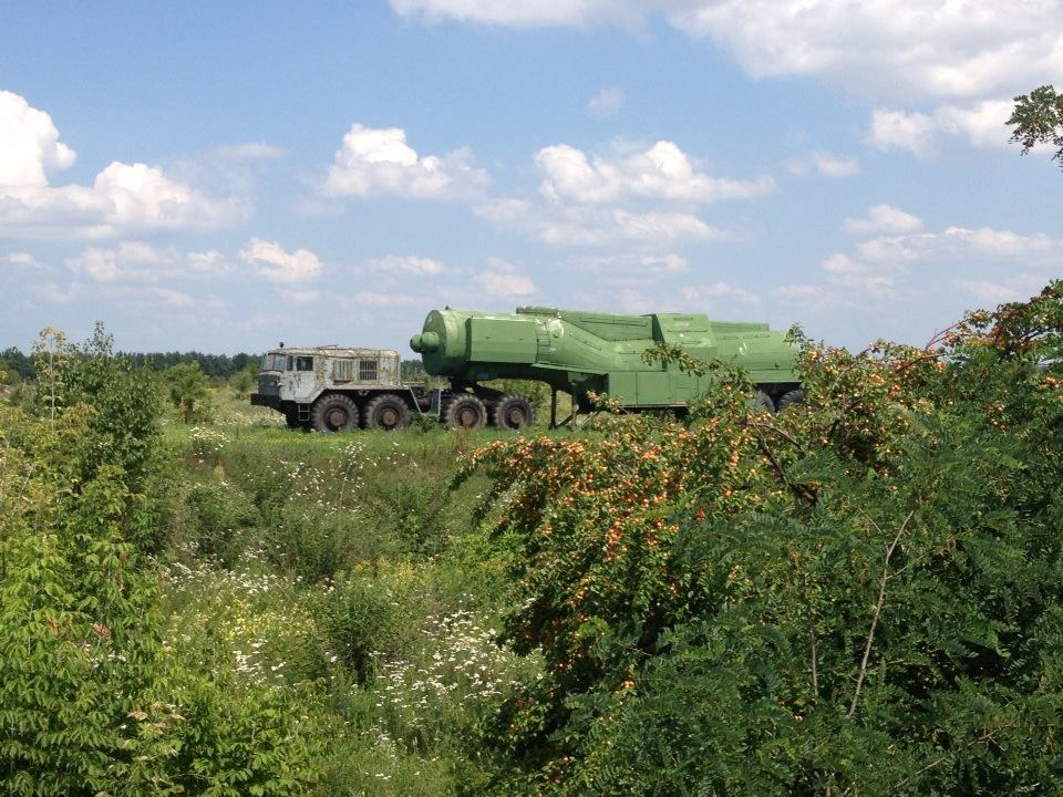 An image of the post-Soviet space: a rusting missile transport truck amidst the wildflowers and wild apricots of the countryside