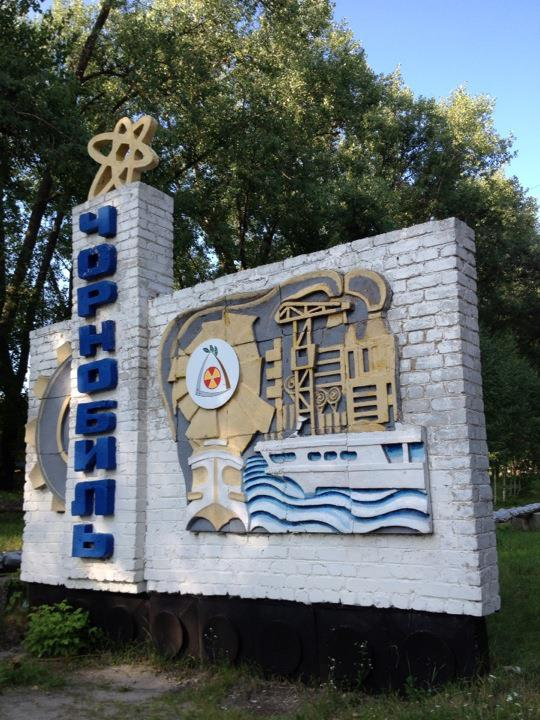 Welcome sign for the city of Chernobyl, featuring symbols of atomic power.