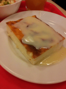 "Zapekanka, described to me as ""Russian cheesecake,"" made with tvorog and topped with sugary icing."