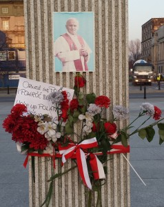 """Wake up Poland and return to God"" - A message (from a concerned citizen) tied with flowers and a Polish-flag colored ribbon around the monument remembering PJP2's historic celebration of the mass and homily here in 1979."