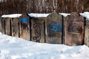 "Graffiti on headstones at Bródno cemetery. On stone slabs someone scribbled: ""Jews are shit,"" ""SS."" There are also drawings of swastikas, pigs and Stars of David hanging on gallows."