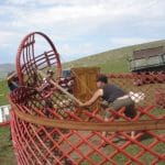 4. A strong man is chosen to raise the yurt's central roof structure. To do so, he uses a pole and ropes for leverage.