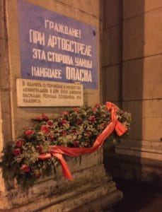 """A WWII era sign still preserved on Nevsky Prospect in St. Petersburg. It warns, """"Citizens! During shelling this side of the street is most dangerous."""" Citizens of St. Petersburg continue to leave flowers by the sign."""